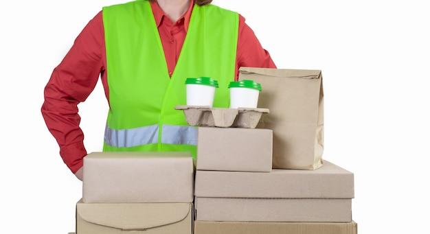 Deliver jest w zielonej kamizelce trzymającej papierowe pudełka i pojemnik na wynos z dwoma białymi kubkami kawy.