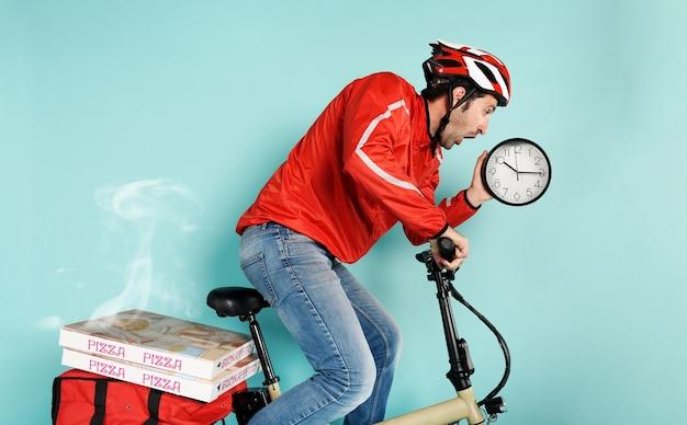 Deliveryman jeździ szybko na rowerze elektrycznym, aby dostarczyć pizzę i uniknąć opóźnień