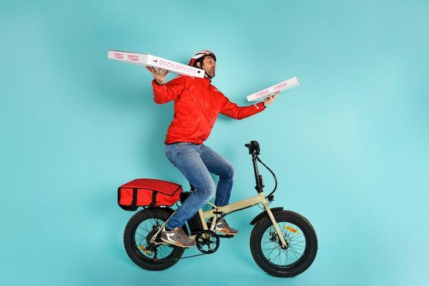 Deliveryman jeździ szybko na rowerze elektrycznym, aby dostarczyć pizzę