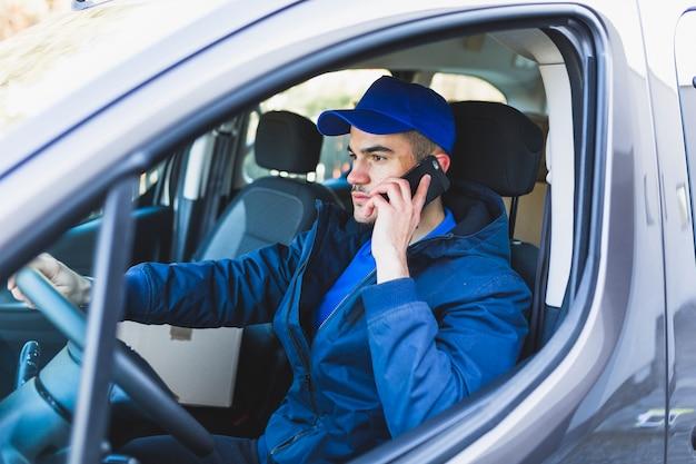 Deliveryman ma rozmowę telefoniczną w samochodzie