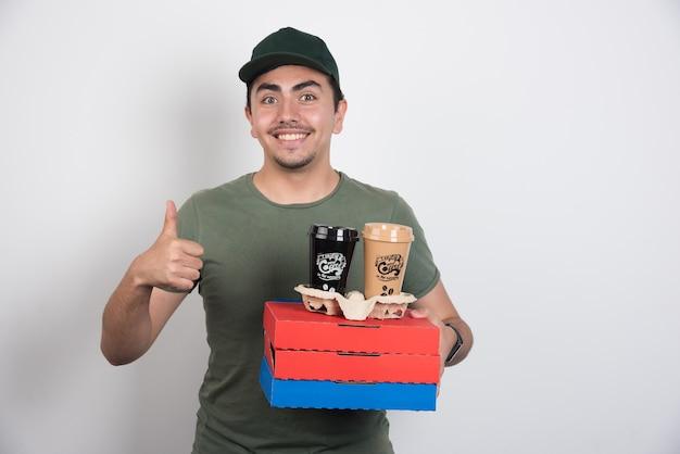 Deliveryman robiący kciuki do góry i trzymający pizzę i kawę.