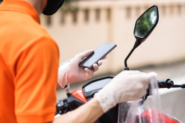 Deliveryman sprawdza lokalizację klienta za pomocą smartfona podczas covid19