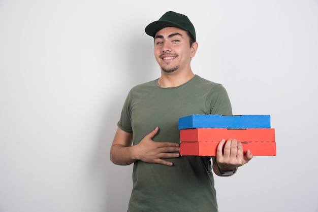 Deliveryman z pudełkami po pizzy, trzymając jego żołądek na białym tle.