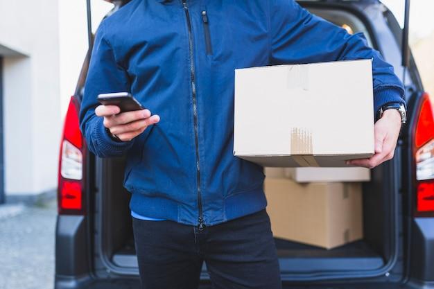 Deliveryman z pudełkiem za pomocą telefonu
