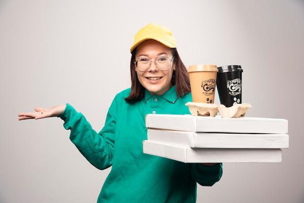 Deliverywoman gospodarstwa karton filiżanek kawy na białym. zdjęcie wysokiej jakości