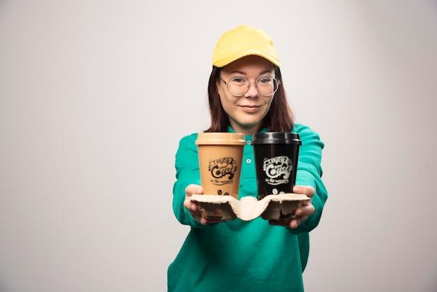 Deliverywoman oferuje karton filiżanek kawy na białym. zdjęcie wysokiej jakości