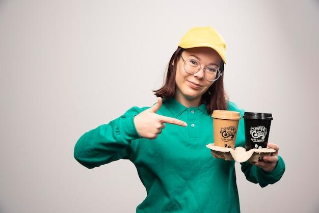 Deliverywoman pokazano karton filiżanek kawy na białym. zdjęcie wysokiej jakości