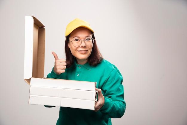 Deliverywoman pokazuje kciuk i trzyma kartony pizzy na białym. zdjęcie wysokiej jakości
