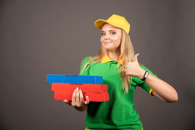 Deliverywoman trzymając kartony pizzy i pokazując kciuk do góry.
