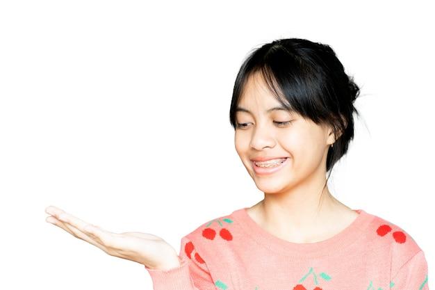 Dental brace dziewczyna uśmiechając się i patrząc na kamery na białym tle, ona czuje się szczęśliwa i ma dobre nastawienie do dentysty. motywuj dzieci, by się nie bały, gdy muszą iść do kliniki dentystycznej.
