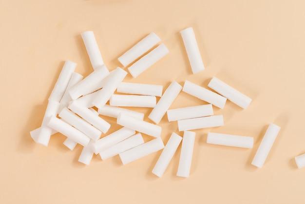 Dental white sterylne wymazy stomatologiczne na beżowym tle.