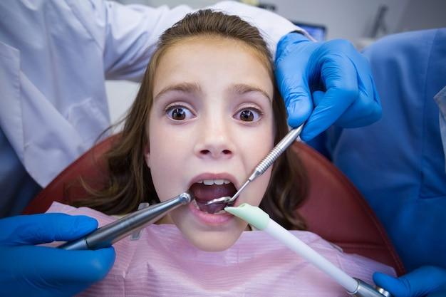 Dentyści badający młodego pacjenta z narzędziami