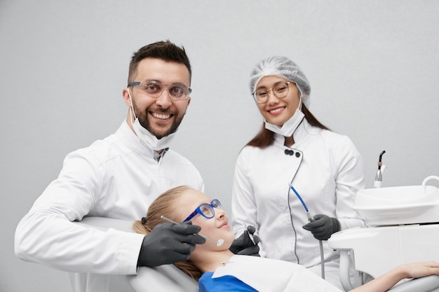 Dentyści patrząc na kamery i śmiejąc się podczas leczenia zębów