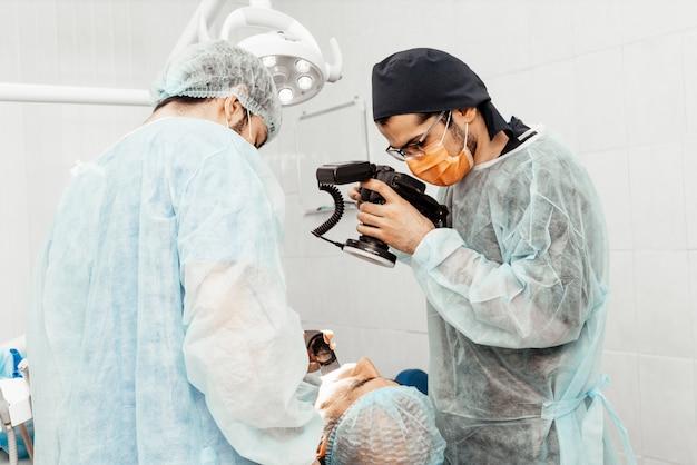 Dentyści wykonają operację, umieszczenie implantu. prawdziwa operacja. ekstrakcja zęba, implanty. profesjonalny uniform i wyposażenie dentysty. opieka zdrowotna wyposażenie miejsca pracy lekarza. stomatologia