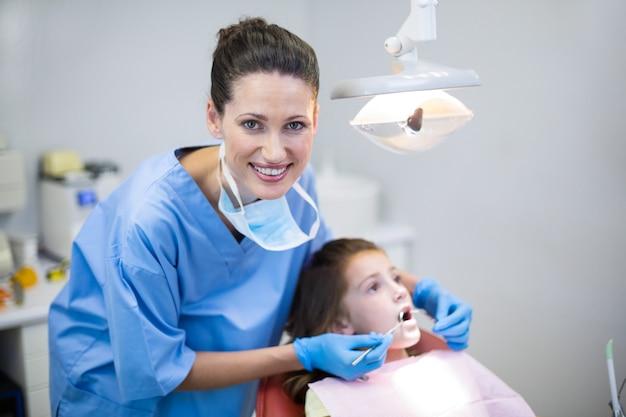 Dentysta bada młodego pacjenta z narzędziami w klinice dentystycznej