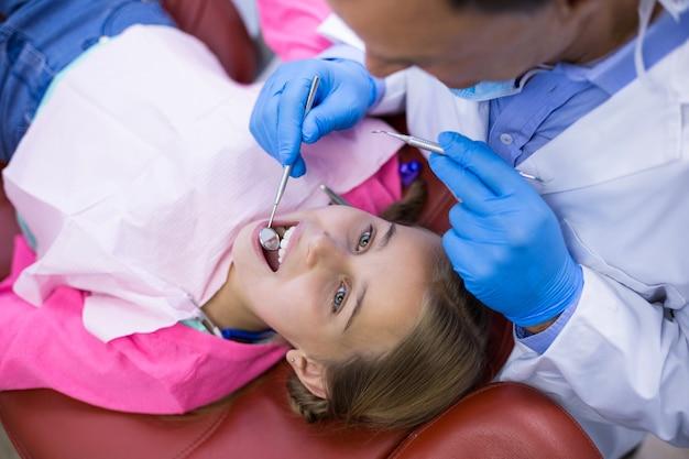 Dentysta bada młodego pacjenta z narzędziami