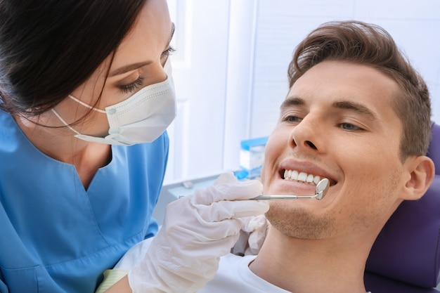 Dentysta bada zęby pacjenta w klinice