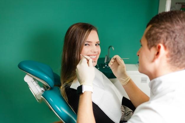 Dentysta bada zęby swojego pacjenta. atrakcyjna dziewczyna jest badana przez dentystę