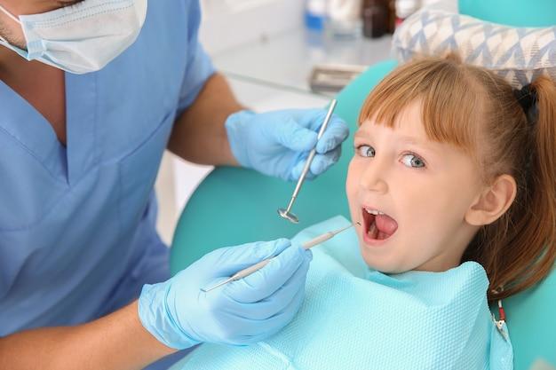 Dentysta badający zęby małej dziewczynki w klinice