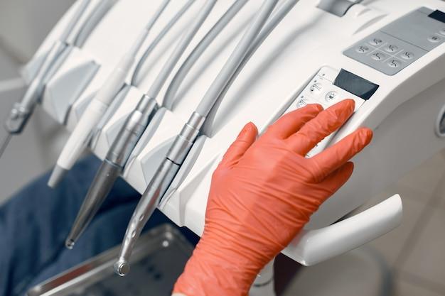 Dentysta bierze instrumenty. lekarz w rękawicach ochronnych. medyk używa urządzenia