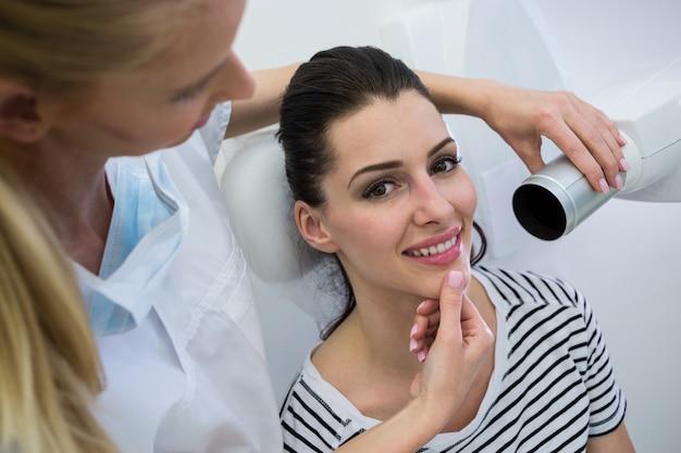Dentysta bierze żeńskiego pacjenta zębu promieniowanie rentgenowskie