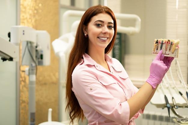 Dentysta demonstruje układ implantów. młoda dentysta w swoim miejscu pracy, prezentacja pracy. chory ząb, próchnica, zapalenie miazgi.