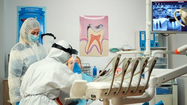 Dentysta dziecięcy w kombinezonie ochronnym zapala lampę do czasu badania, podczas gdy mały pacjent otwiera usta. zespół medyczny rozmawia podczas koronawirusa w osłonie twarzy, kombinezonie, masce i rękawiczkach