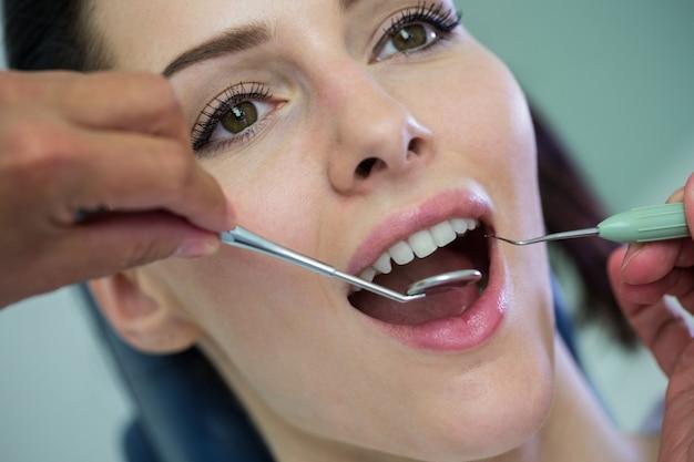 Dentysta egzamininuje żeńskiego pacjenta z narzędziami