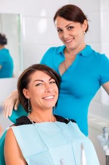 Dentysta i jej szczęśliwy pacjent patrzą w kamerę i uśmiechają się. odbiór u dentysty, zdrowe zęby, szczęśliwy pacjent, piękne zęby.