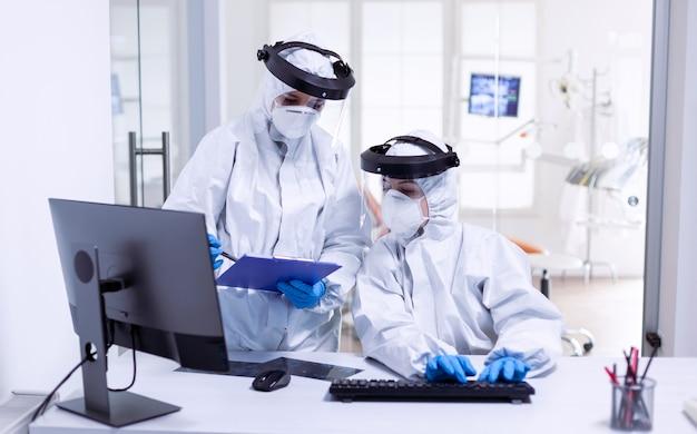 Dentysta i pielęgniarka podczas globalnej epidemii w kombinezonie chroniącym przed zakażeniem covid-19. zespół medyczny noszący sprzęt ochronny przed pandemią koronawirusa w recepcji stomatologicznej jako środek ostrożności