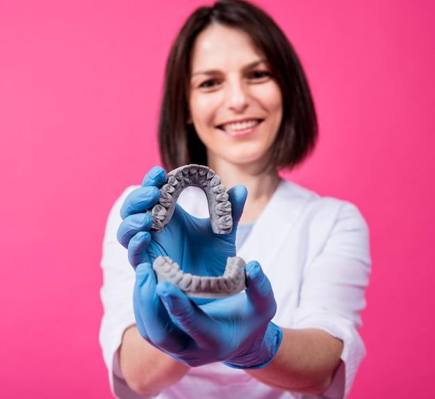 Dentysta kobieta trzyma w rękach modele gipsu dentystycznego