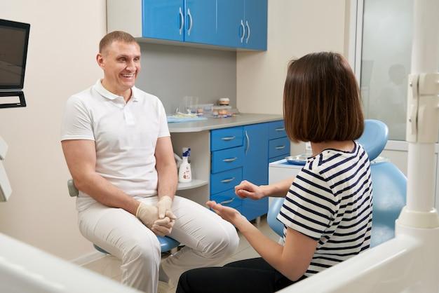 Dentysta konsultuje pacjenta siedzącego na krześle w swoim gabinecie