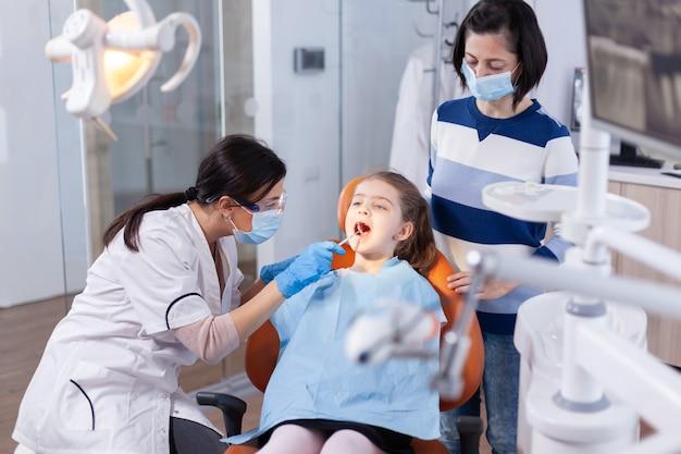 Dentysta korzystający z lustra w trakcie badania jamy ustnej dziecka siedzącego na fotelu dentystycznym. lekarz stomatolog podczas konsultacji jamy ustnej dziecka w gabinecie stomatologicznym z wykorzystaniem nowoczesnych technologii.