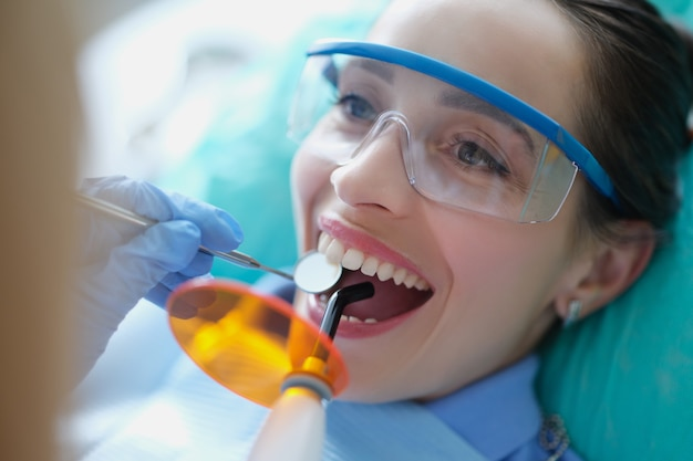 Dentysta leczący zęby pacjentce za pomocą światła utwardzającego i instrumentów dentystycznych