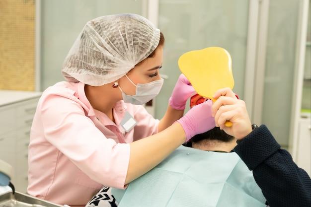 Dentysta młoda kobieta leczy pacjenta mężczyznę. lekarz używa jednorazowych rękawiczek, maski, czapki i okularów ochronnych.