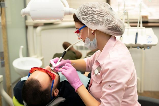 Dentysta młoda kobieta leczy pacjenta mężczyznę. lekarz używa jednorazowych rękawiczek, maski i czapki. dentysta pracuje w jamie ustnej pacjenta, używa profesjonalnego narzędzia