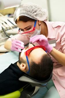 Dentysta młoda kobieta leczy pacjenta mężczyznę. lekarz używa jednorazowych rękawiczek, maski i czapki.