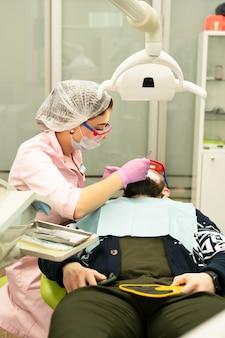 Dentysta młoda kobieta leczy pacjenta mężczyznę.