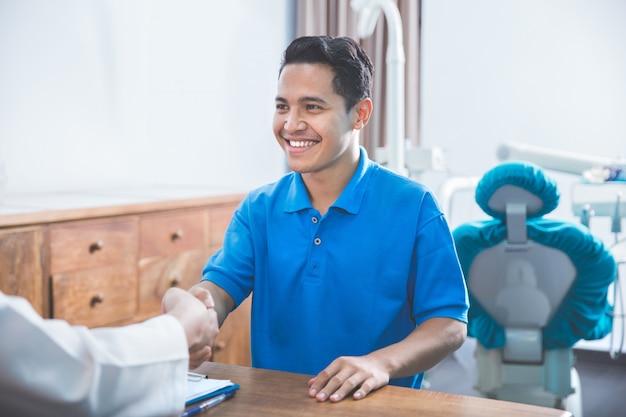 Dentysta mówi do swojego pacjenta w klinice opieki dentystycznej i drżenie rąk