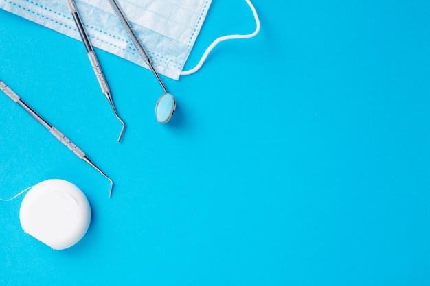 Dentysta narzędzia lub instrumenty odkrywców dentystycznych, lusterko dentystyczne, nić dentystyczna i procedura maska na jasnoniebieskim tle. wolna przestrzeń.