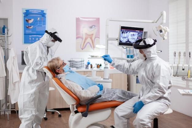 Dentysta noszący sprzęt przeciw koronawirusowi rozmawiający o higienie zębów ze starszym pacjentem