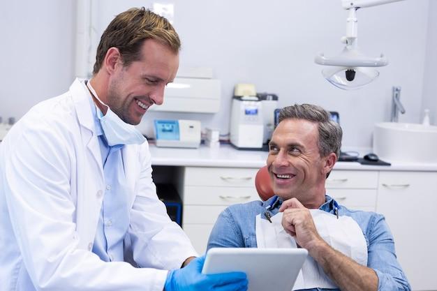 Dentysta omawiając cyfrowy tablet z pacjentem