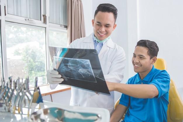 Dentysta opowiada z jego pacjentem wyjaśnia radiogram radiologiczny