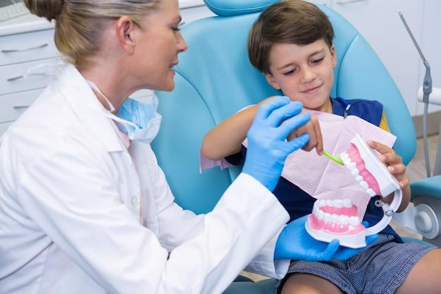 Dentysta patrząc na chłopca szczotkującego protezy