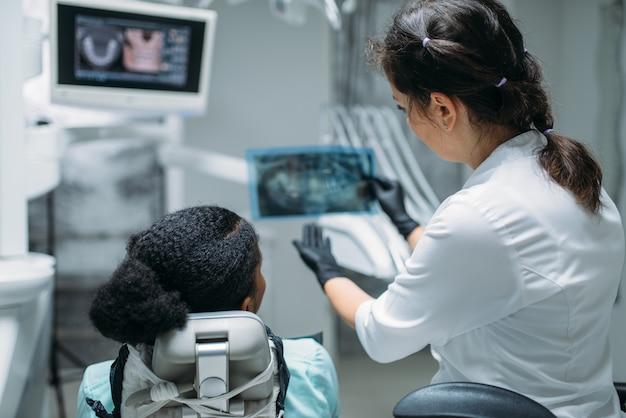 Dentysta patrząc na zdjęcie rentgenowskie, klinika stomatologiczna
