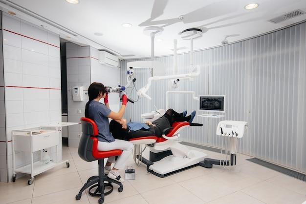 Dentysta patrzy przez mikroskop i wykonuje operację na pacjencie.