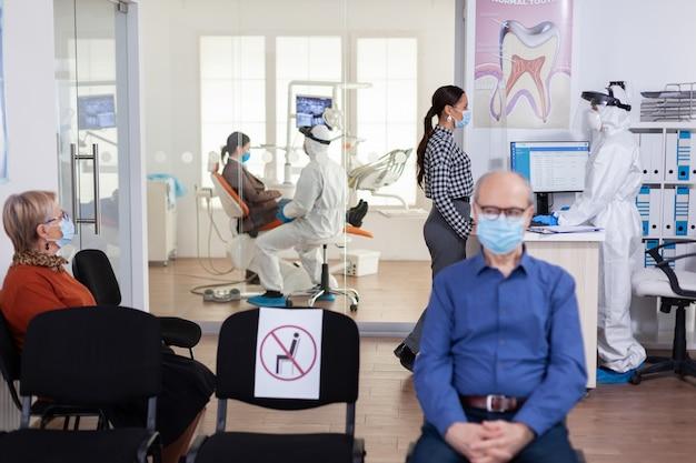 Dentysta pielęgniarka ubrana w garnitur ppe z twarzą shiled omawianie z pacjentem w poczekalni stomatologii. osoby utrzymujące dystans społeczny jako profilaktyka podczas epidemii koronawirusa.