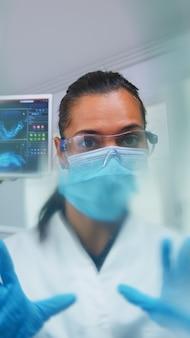 Dentysta pochylając się nad pacjentem zakładającym maskę tlenową przed zabiegiem w gabinecie stomatologicznym. lekarz pracujący w nowoczesnej klinice ortodontycznej w masce ochronnej i rękawiczkach podczas sprawdzania opieki zdrowotnej