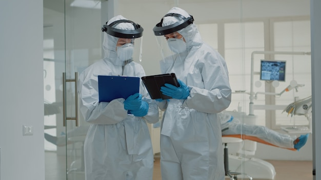 Dentysta podający tabletkę pielęgniarce stomatologicznej przed konsultacją