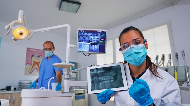 Dentysta pokazujący prześwietlenie zębów tabletu, przeglądające go z pacjentem. lekarz i pielęgniarka pracują razem w nowoczesnej klinice stomatologicznej, wyjaśniając starszej kobiecie zdjęcie radiograficzne zęba za pomocą wyświetlacza notebooka